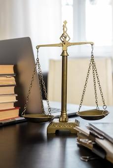 Ufficio di avvocato con bilance, laptop e documenti sul posto di lavoro.