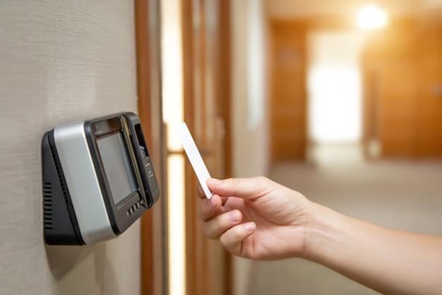 L'uomo dell'ufficio sta usando la carta d'identità per scansionare il controllo di accesso per aprire la porta di sicurezza