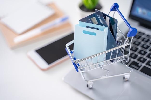 Pagamento online in ufficio, shopping a casa, pagamento elettronico con il concetto di carta di credito, laptop su sfondo bianco tavolo con carrello, primo piano.