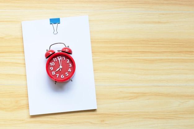 Carta da ufficio con sveglia rossa sul fondo della tavola in legno. vista dall'alto