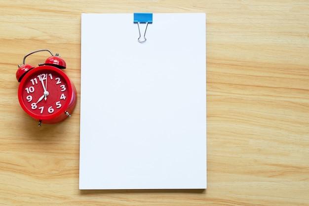 Carta da ufficio con sveglia rossa su sfondo texture in legno.