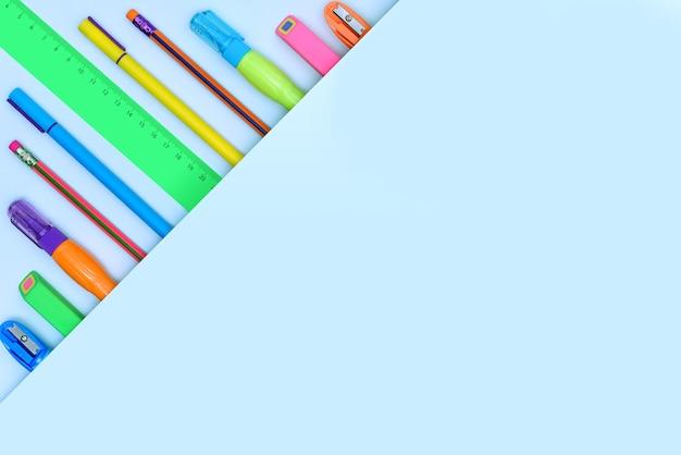 Cancelleria colorata per ufficio e scuola su sfondo blu come bordo d'angolo piegato
