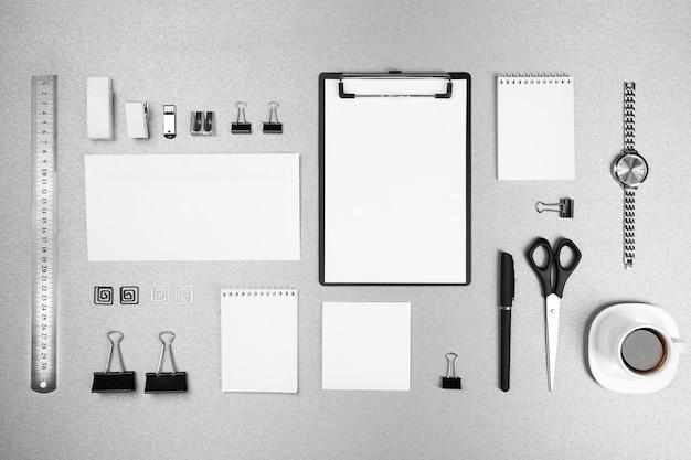 Set da ufficio con fogli di carta bianchi, tazza di caffè, orologio e cancelleria su sfondo grigio