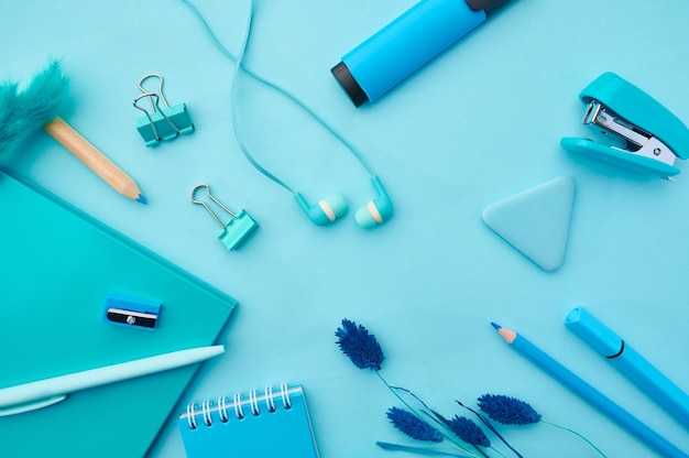 Articoli di cancelleria per ufficio nei toni del blu. accessori per la scuola o l'istruzione, strumenti per scrivere e disegnare, matite e penne, clip e blocco note