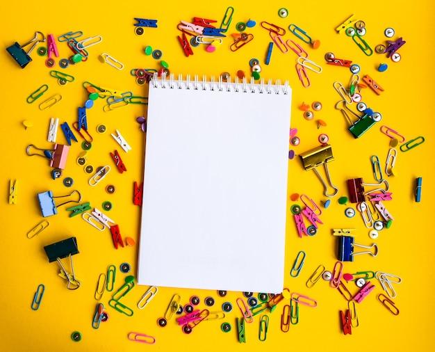 Forniture per ufficio di bottoni colorati e graffette con blocco note vuoto