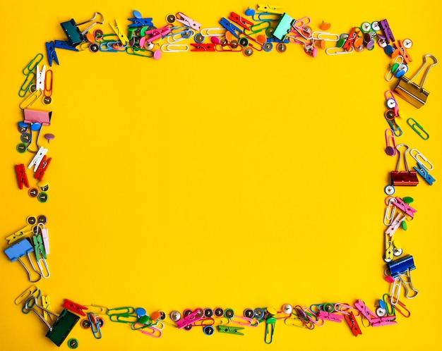 Forniture per ufficio sotto forma di bottoni colorati e graffette