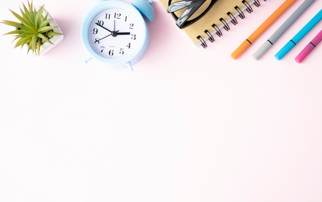Le forniture per ufficio si trovano su uno sfondo rosa. studio a scuola. colore arcobaleno.