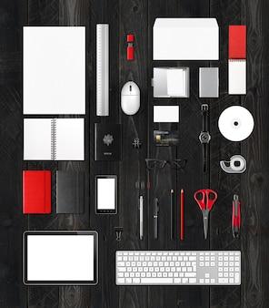 Modello di mockup di forniture per ufficio, isolato su fondo di legno nero