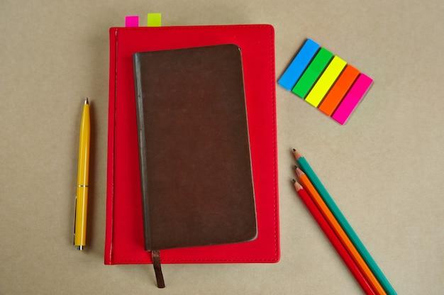 Forniture per ufficio, quaderni, penne, matite, segnalibri, su uno sfondo di carta