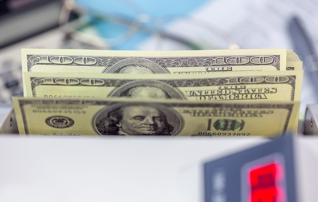 Forniture per ufficio sulla scrivania in defocus. banconote a 100 usd nel contatore