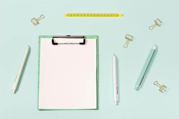 Forniture per ufficio, tablet di carta con clip, penne, righello e graffette metalliche. concetto di scuola e istruzione.