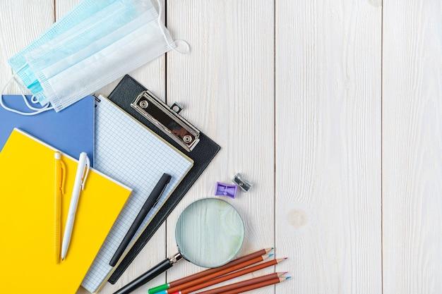 Forniture per ufficio e maschere protettive su sfondo bianco. vista dall'alto, copia dello spazio. di nuovo a scuola.