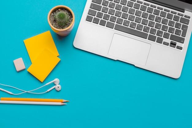 Scrivania da tavolo con forniture su sfondo blu, vista dall'alto e copia spazio