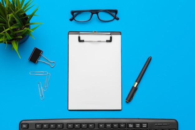 Scrivania da tavolo con forniture su blu, vista dall'alto e copia spazio per il testo