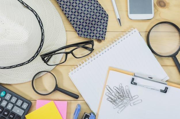 Tavolo ufficio vista dall'alto con gli occhiali, taccuino, lente di ingrandimento e telefono cellulare