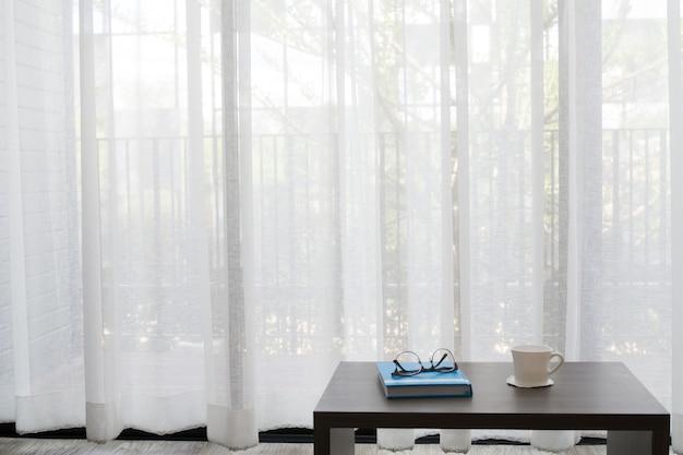 Tavolo da ufficio su finestre bianche sullo sfondo della tenda