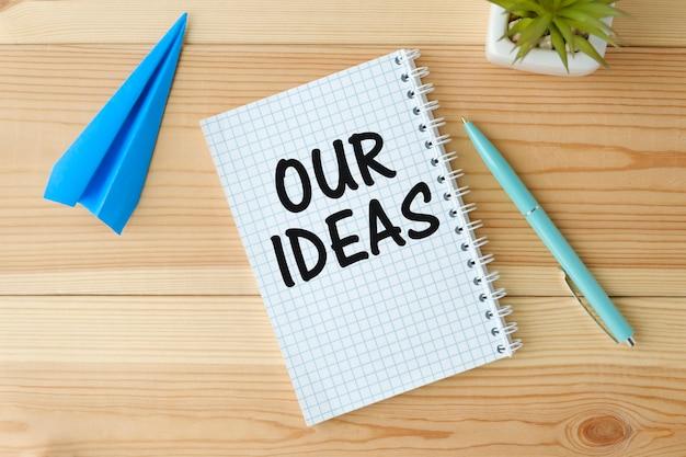 Tavolo da ufficio con penna, calcolatrice e foglio vuoto con testo le nostre idee.
