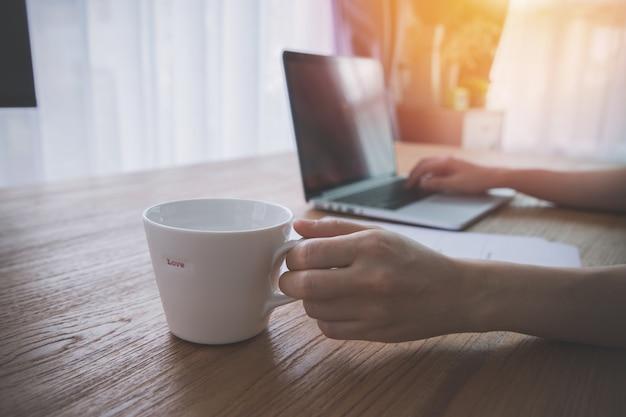 Tavola dell'ufficio con informazioni di carta del riassunto e giovane donna asiatica che per mezzo del computer portatile.