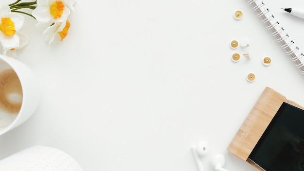 Lavoro d'ufficio, concetto di piatto di istruzione laici con clip, telefono, auricolari, tazza di caffè e fiori di tulipano, matita e blocco note su priorità bassa bianca.