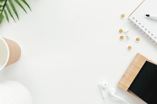 Lavoro d'ufficio, concetto di piatto di istruzione laici con clip, telefono, auricolari, coppa e fiori di tulipano su sfondo bianco.