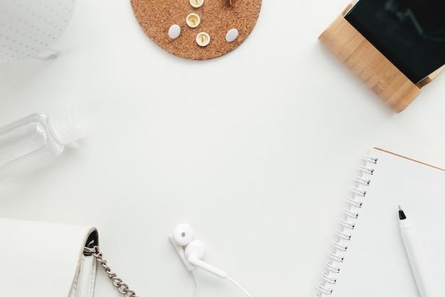 Lavoro d'ufficio, concetto di piatto laico di istruzione con disinfettante, clip, telefono, auricolari e borsa da donna su priorità bassa bianca