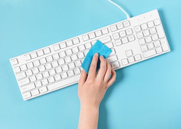 L'impiegato disinfetta e pulisce la tastiera funzionante con un tovagliolo blu antibatterico.