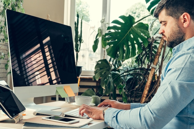 Impiegato che fa il suo lavoro seduto al suo tavolo di lavoro con un computer