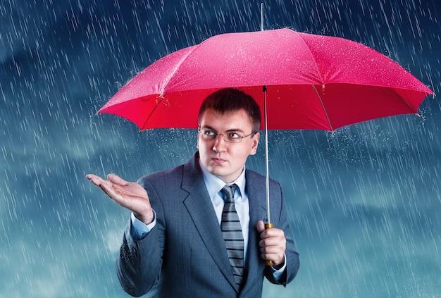 Impiegato che si nasconde sotto un ombrello