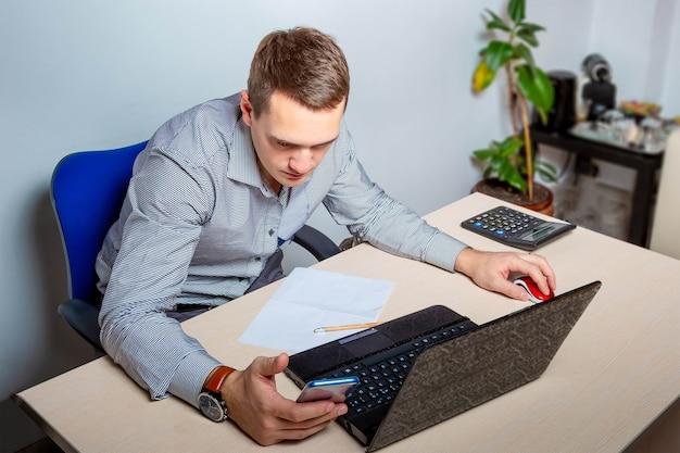 L'impiegato esamina attentamente il telefono giovane uomo d'affari in ufficio si siede al tavolo e lavora sul laptop