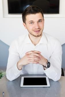 Impiegato maschio con tablet pc mock up sul tavolo, insegnante uomo in tuta sorridente