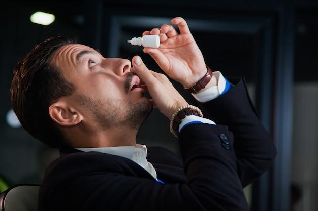 Impiegato che soffre di sindrome dell'occhio secco, collirio con lacrime artificiali