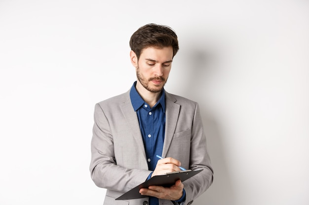 Impiegato in tuta iscritto negli appunti, prendendo appunti sulla riunione, in piedi su sfondo bianco.