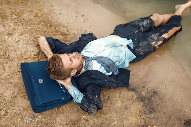 Impiegato in vestito strappato che riposa sulla spiaggia sull'isola deserta. rischio aziendale, crollo o concetto di fallimento