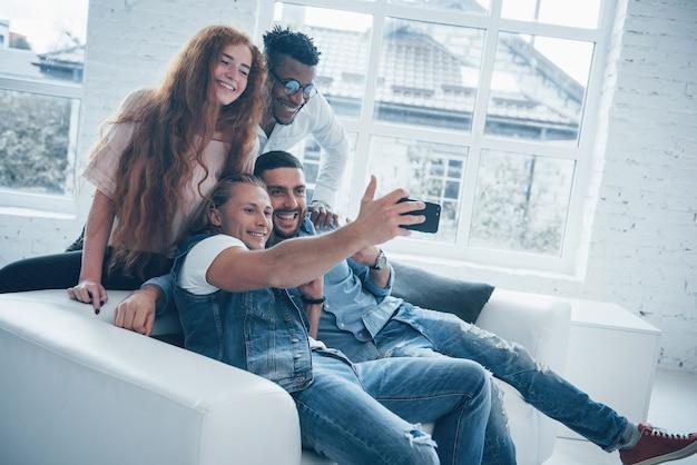 Gli impiegati hanno una pausa. giovani amici allegri che prendono i selfies sul sofà e sull'interno bianco