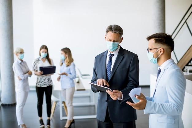 Gli impiegati hanno una riunione in ufficio con maschere facciali come protezione dal coronavirus