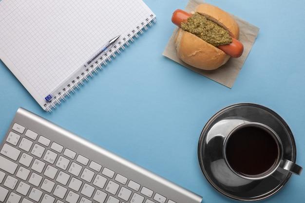 Mock-up sul posto di lavoro dell'ufficio - caffè, hot dog snack, quaderno, tastiera sul tavolo blu, vista piana, vista dall'alto