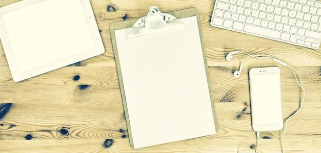 Ufficio di lavoro con appunti, carta, tastiera, pad, telefono, cuffie. immagine tonica in stile vintage