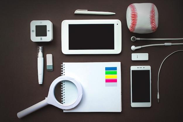 Posto di lavoro di ufficio con laptop, notebook, forniture per ufficio e cancelleria su sfondo marrone scuro. soluzione, pianificazione aziendale, creatività, design, apprendimento, avvio o lavoro concetto di vista dall'alto piatto.