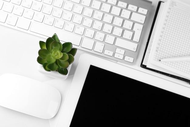 Posto di lavoro in ufficio con tablet e pianta in vaso da vicino