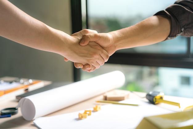 Il lavoro di squadra dell'ufficiale è felice e stringe le mani per celebrare nella costruzione di edifici di successo