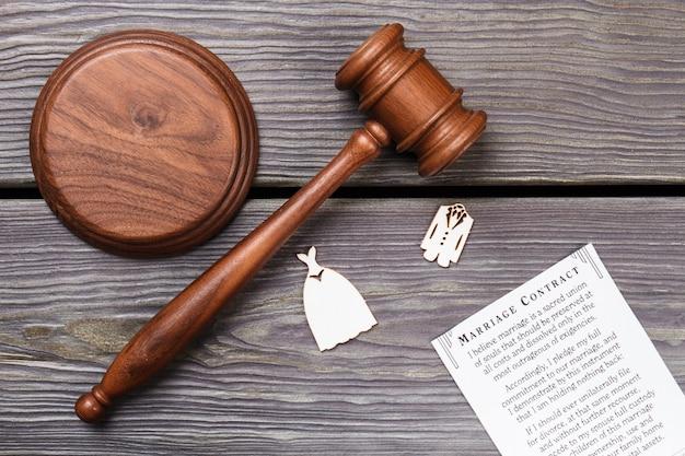 Concetto di matrimonio ufficiale. contratto di matrimonio con martelletto di legno sul tavolo piatto laici.