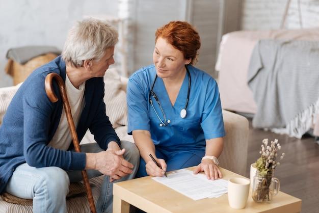 Procedura ufficiale. gentiluomo invecchiato motivato intelligente che desidera assumere un operatore sanitario per cure domiciliari e venire con i termini prima di firmare i documenti