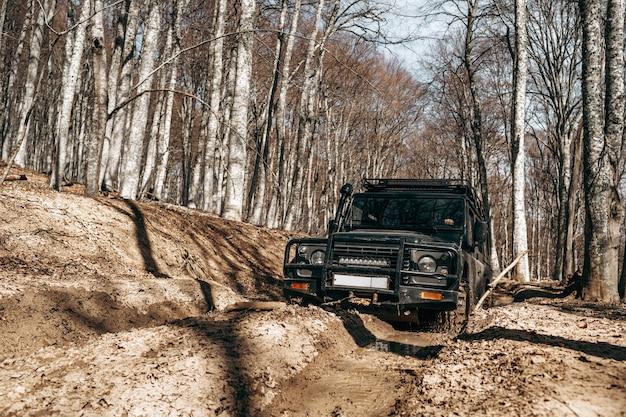 Auto fuoristrada che guida attraverso la strada forestale di fango