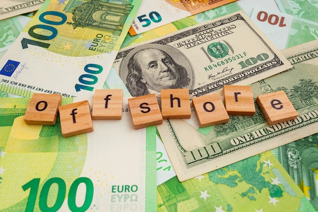 Iscrizione offshore su cubi di legno sulla trama di dollari americani e banconote in euro