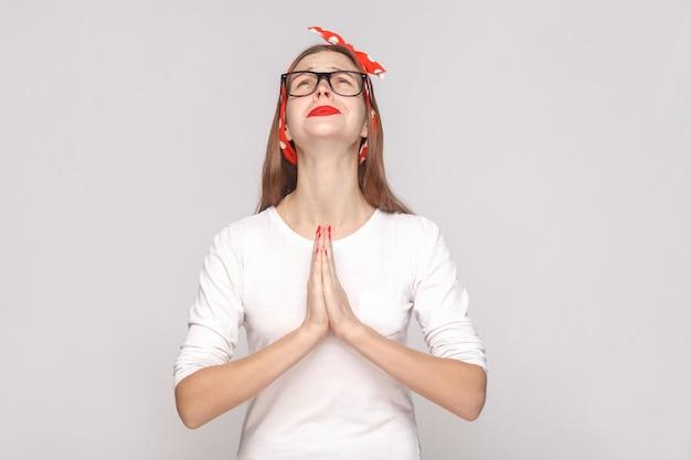 Oh mio dio, per favore aiutami. ritratto di bella giovane donna emotiva in maglietta bianca con lentiggini, occhiali neri, labbra rosse e fascia per la testa. colpo dello studio al coperto, isolato su sfondo grigio chiaro.