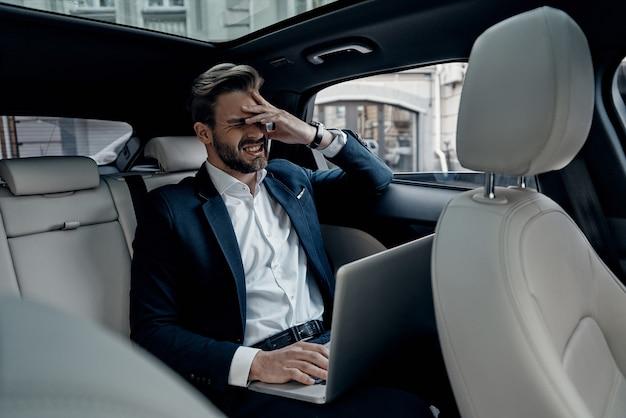 Oh no! giovane frustrato in tuta intera che lavora usando il laptop e copre il viso con la mano mentre è seduto in macchina