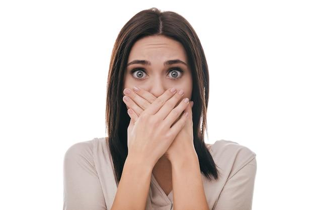 Oh no! giovane donna frustrata che copre la bocca con le mani e fissa la telecamera mentre si trova in piedi su sfondo bianco