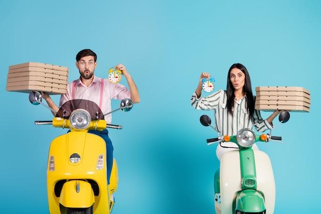 Oh no! foto di funny lady guy guidare due vintage retrò ciclomotore trasportare carta pizza scatole corriere occupazione controllare il tempo mancare consegna abbigliamento formale vestito isolato blu parete di colore
