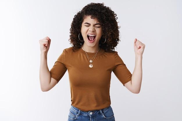 Oh si. eccitato felice emotiva donna capelli scuri ricci urlare ad alta voce felicità gioia raggiungere il successo buon affare chiudere gli occhi urlare sì stringere i pugni trionfo allegria celebrare la vittoria vincendo lotteria