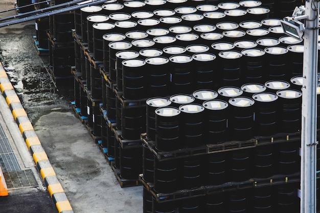 Barili di petrolio neri o fusti chimici impilati orizzontalmente